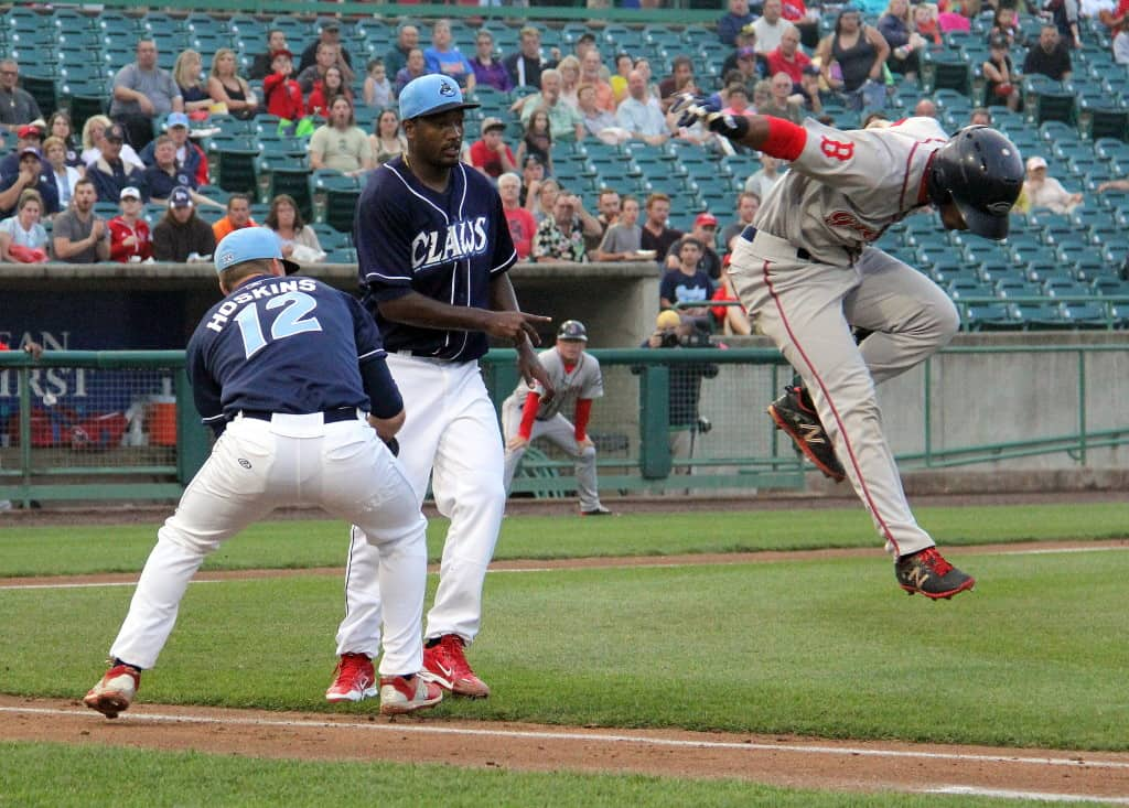 Greenville's Joseph Monge hurdles two Lakewood players on his way to first base.